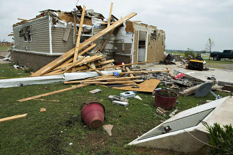 A home lies in ruins near  a storm shelter in the foreground after a tornado yesterday tore through the area for the second time in three years, on April 28, 2014 in Vilonia, Arkansas. After deadly tornadoes ripped through the region, leaving more than a dozen dead, Mississippi, Arkansas, Texas, Louisiana and Tennessee are all under watch as multiple storms over the next few days are expected.  Photo: Wesley Hitt, Getty Images