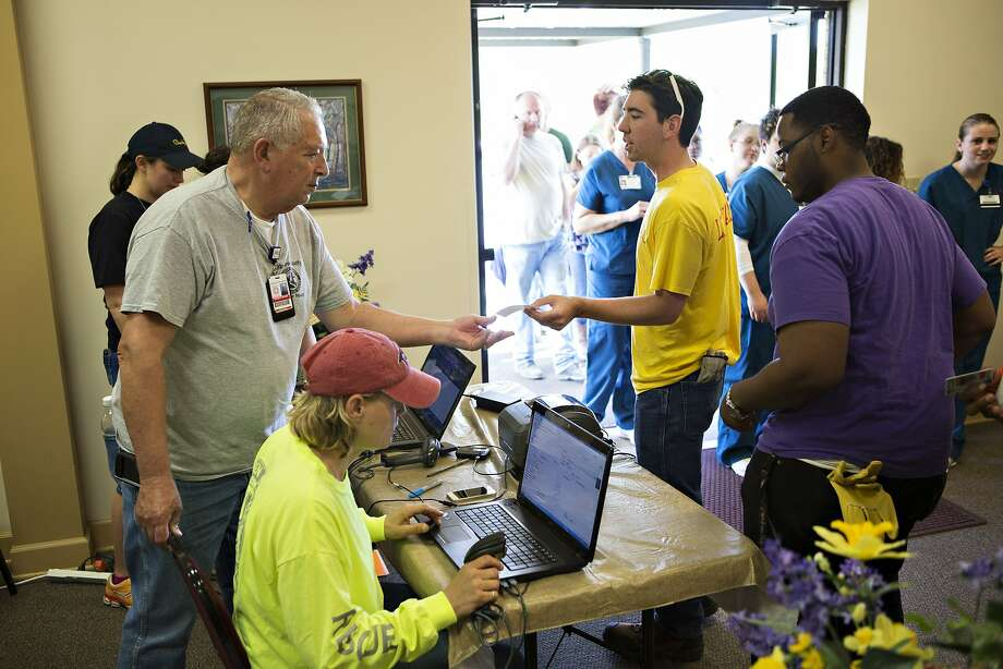 Ken Brown hands out IDs at Beryl Baptist Church to volunteers after a tornado yesterday tore through the area for the second time in three years, on April 28, 2014 in Vilonia, Arkansas. After deadly tornadoes ripped through the region, leaving more than a dozen dead, Mississippi, Arkansas, Texas, Louisiana and Tennessee are all under watch as multiple storms over the next few days are expected.  Photo: Wesley Hitt, Getty Images