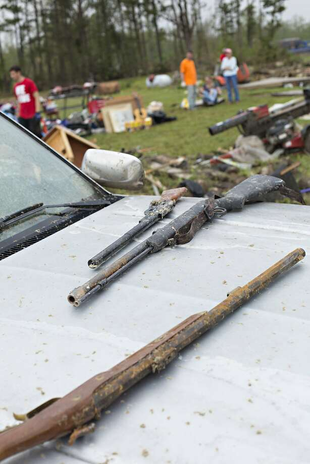 Salvaged guns sit on the hood of a car after a tornado yesterday tore through the area for the second time in three years, on April 28, 2014 in Vilonia, Arkansas. After deadly tornadoes ripped through the region, leaving more than a dozen dead, Mississippi, Arkansas, Texas, Louisiana and Tennessee are all under watch as multiple storms over the next few days are expected. Photo: Wesley Hitt, Getty Images
