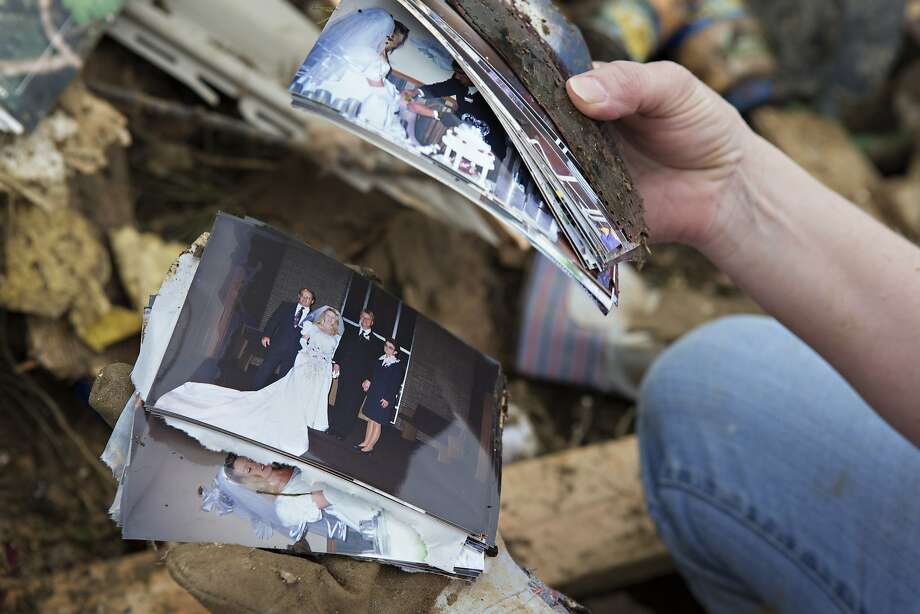Lisa Taney, a volunteer, goes through wedding photos found in the mud near a destroyed trailer after a strong tornado went through the area on April 27 for the second time in three years on April 28, 2014 in Vilonia, Arkansas. After deadly tornadoes ripped through the area and have left over a dozen dead, Mississippi, Arkansas, Texas, Louisiana, and Tennessee are all under watch as multiple storms over the next few days are expected. Photo: Wesley Hitt, Getty Images