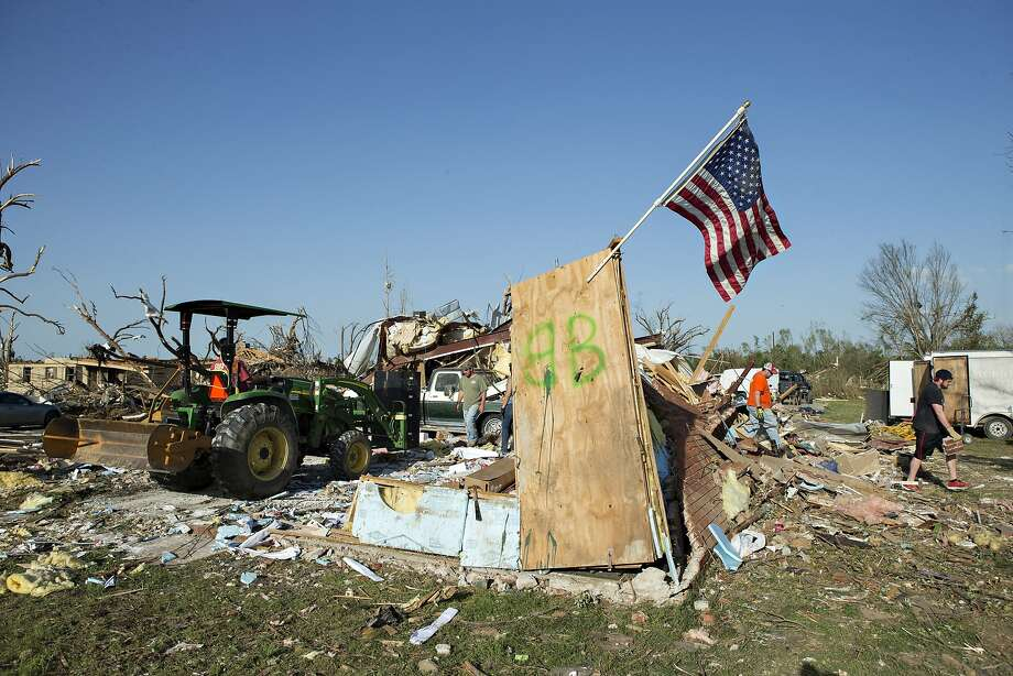 Homeowners and volunteers clean up damage after a tornado yesterday tore through the area for the second time in three years, on April 28, 2014 in Mayflower, Arkansas. After deadly tornadoes ripped through the region leaving more than a dozen dead, Mississippi, Arkansas, Texas, Louisiana and Tennessee are all under watch as multiple storms over the next few days are expected.  Photo: Wesley Hitt, Getty Images