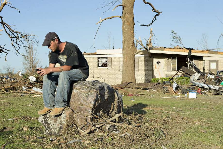 William Higgins sits on a stump outside his grandfather's house that was destroyed by a tornado yesterday that tore through the area for the second time in three years is shown, on April 28, 2014 in Mayflower, Arkansas. After deadly tornadoes ripped through the region leaving more than a dozen dead, Mississippi, Arkansas, Texas, Louisiana and Tennessee are all under watch as multiple storms over the next few days are expected. Photo: Wesley Hitt, Getty Images