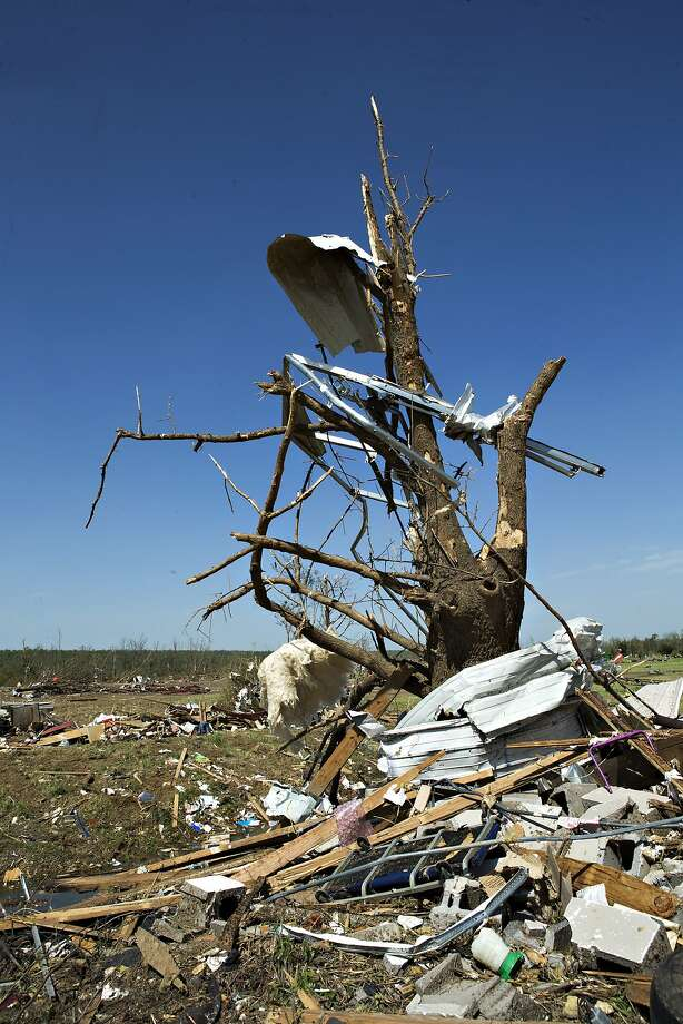 Debris hangs from a tree after a tornado yesterday tore through the area for the second time in three years, on April 28, 2014 in Vilonia, Arkansas. After deadly tornadoes ripped through the region, leaving more than a dozen dead, Mississippi, Arkansas, Texas, Louisiana and Tennessee are all under watch as multiple storms over the next few days are expected. Photo: Wesley Hitt, Getty Images