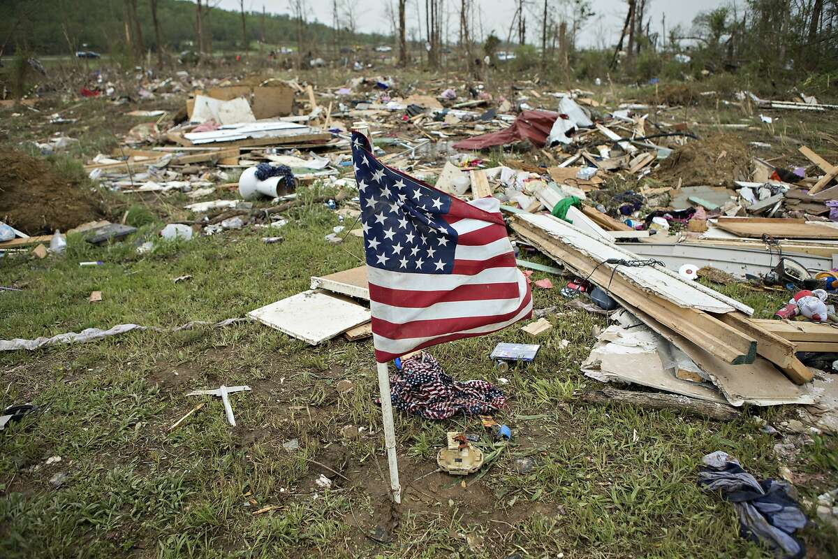Flag that was found in debris was placed by volunteers working to help clean up after a strong tornado went through the area on April 27 for the second time in three years on April 28, 2014 in Vilonia, Arkansas. After deadly tornadoes ripped through the area and have left over a dozen dead, Mississippi, Arkansas, Texas, Louisiana, and Tennessee are all under watch as multiple storms over the next few days are expected.