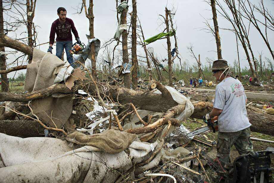 Eric Baker and Ron Smith use chainsaws and cut up trees after a strong tornado went through the area on April 27 for the second time in three years on April 28, 2014 in Vilonia, Arkansas. After deadly tornadoes ripped through the area and have left over a dozen dead, Mississippi, Arkansas, Texas, Louisiana, and Tennessee are all under watch as multiple storms over the next few days are expected.  Photo: Wesley Hitt, Getty Images