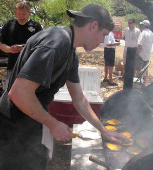 Clellan Cook of Big Bob's Burgers preps hamburger patties, for free burgers, at the Olmos Park Fiesta Frolic on Sunday at Alameda Circle. Big Bob's has locations on Hildebrand near Olmos Park, and in downtown. Photo: Edmond Ortiz / Alamo Heights Wee