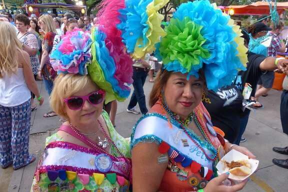 Marci Aguirre, left, and Paula Gallegos-Denton wear Fiesta hats the annual Taste of the Northside, a food-friendly event at the parking lot of The Club at Sonterra, on Wednesday, April 23, 2014.
