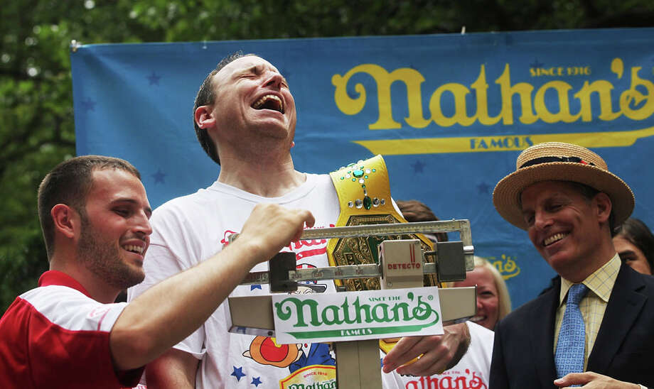 Men's world record holder Joey Chestnut laughs as he is weighed at the Nathan's Famous Fourth of July International Hot Dog Eating Contest weigh-in ceremony on July 3, 2013 in the Brooklyn borough of New York City. Photo: Mario Tama, Getty Images / 2013 Getty Images