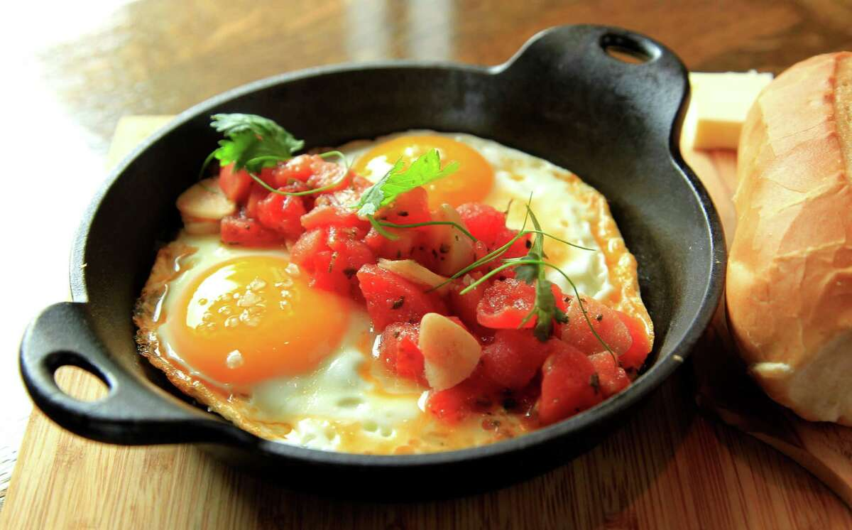 The Huevos con Tomate, two baked eggs topped with peeled tomatoes, garlic and olive oil, is served with french baguette and butter at Andes Cafe.