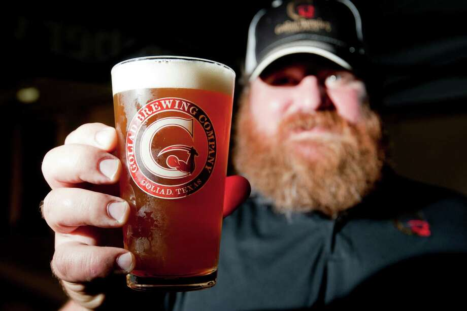 Mark Nichols with the Goliad Brewing Company holds a pint of Redfish IPA at the Faust Distributing retailer trade show Thursday, April 24, 2014, in Houston. ( Johnny Hanson / Houston Chronicle ) Photo: Johnny Hanson / © 2014  Houston Chronicle