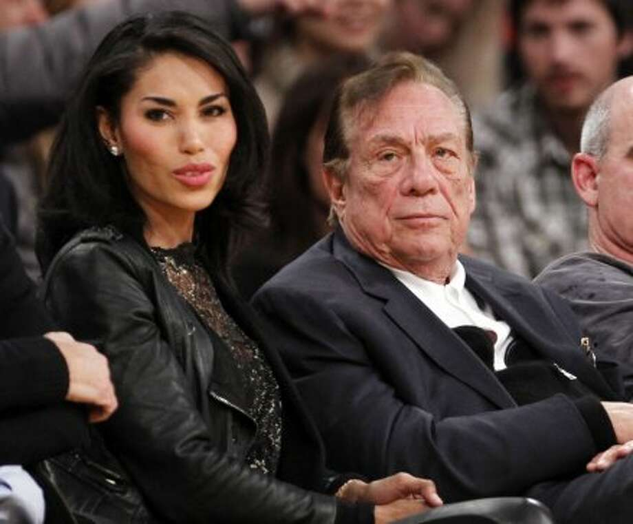 In this Dec. 19, 2010, file photo, Los Angeles Clippers owner Donald Sterling, third right, sits with V. Stiviano, left, as  they watch the Clippers play the Los Angeles Lakers during an NBA preseason basketball game in Los Angeles. NBA commissioner Adam Silver announced Tuesday, April 29, 2014, that he is banning the owner for life from the Clippers organization over racist comments in recording. Photo: Danny Moloshok, Associated Press