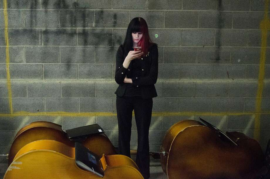 The bass in the basement:Alana Collins fiddles with her phone amid a trio of bass before the Flint School of 