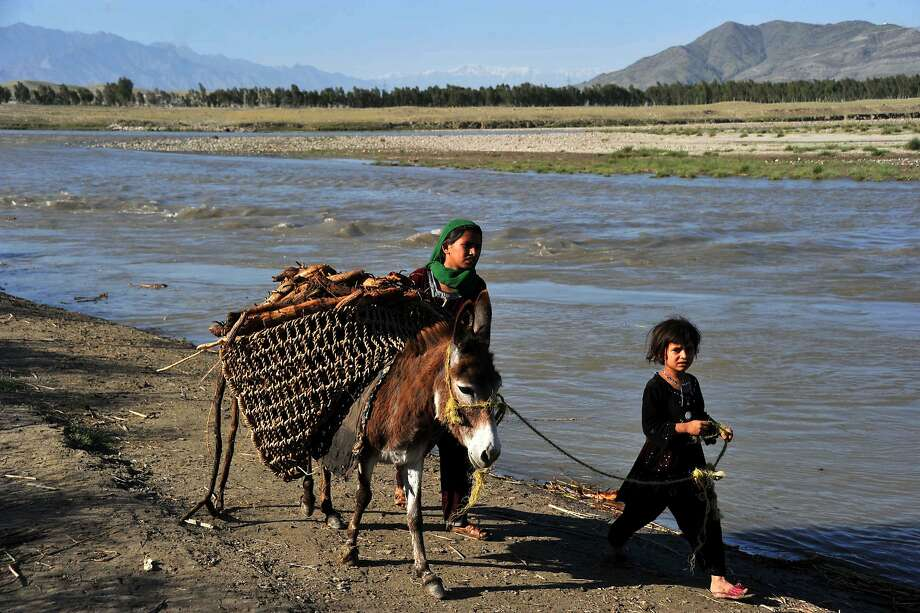 With no parental supervision,Afghan Kuchi children lead their donkey across a river on the outskirts of Jalalabad. The 