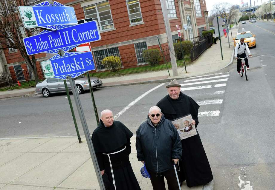 The Rev. Stefan Morawski, the Rev. George Maslar and the Rev. Michal Socha, from left, stand in front of the newly named St. John Paul II Corner Tuesday, April 29, 2014, in Bridgeport, Conn. The intersection of Kossuth Street and Pulaski Street was renamed in honor of Pope John Paul II on Sunday, to mark his canonization. Photo: Autumn Driscoll / Connecticut Post