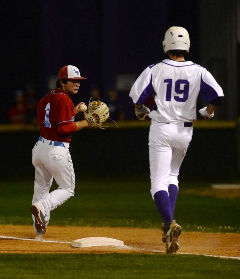 Lumberton's Trey Godeaux, No. 1, looks back at Port Neches-Groves' Carter Henry, No. 19, after running the ball into first base to out Henry during Friday's game. The Port Neches-Groves High School baseball team played against Lumberton at Port Neches-Groves on Friday afternoon. Photo taken Friday, 4/4/14 Jake Daniels/@JakeD_in_SETX