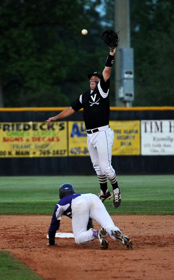 Vidor's Dalton Croft, No. 12, leaps for a catch while Port Neches-Groves' Corbin Coy, No. 11, slides into second base during Friday's game. Vidor played against Port Neches at Vidor on Friday afternoon. Photo taken Friday, 4/18/14 Jake Daniels/@JakeD_in_SETX