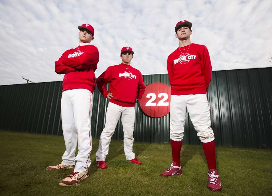 Chase Shugart, junior, Hunter Uzzle, senior, and Keaton Langston, senior, left to right, pose for a picture in the outfield at the Bridge City High School baseball field Thursday afternoon. The Bridge City Cardinals have won 22 district titles in the past, which means expectations are high for this upcoming season. Photo taken Thursday, 2/6/14 Jake Daniels/@JakeD_in_SETX