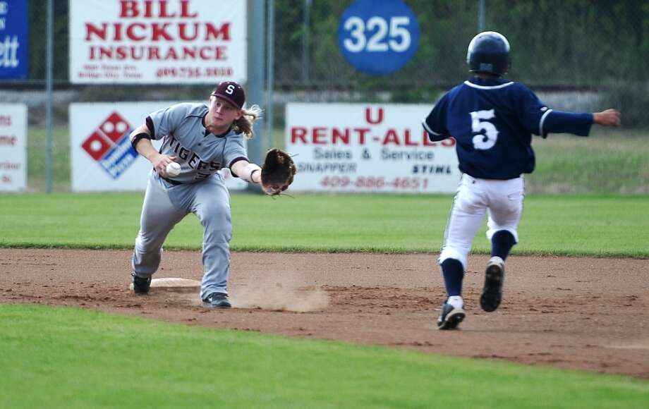 Silsbee's Tyler Powell, No. 3, reaches out from second base for a catch while West Orange-Stark's Payton Robertson, No. 5, starts to go into a slide Monday. The West Orange-Stark High School baseball team played against Silsbee at West Orange-Stark on Monday afternoon. Photo taken Monday, 3/31/14 Jake Daniels/@JakeD_in_SETX