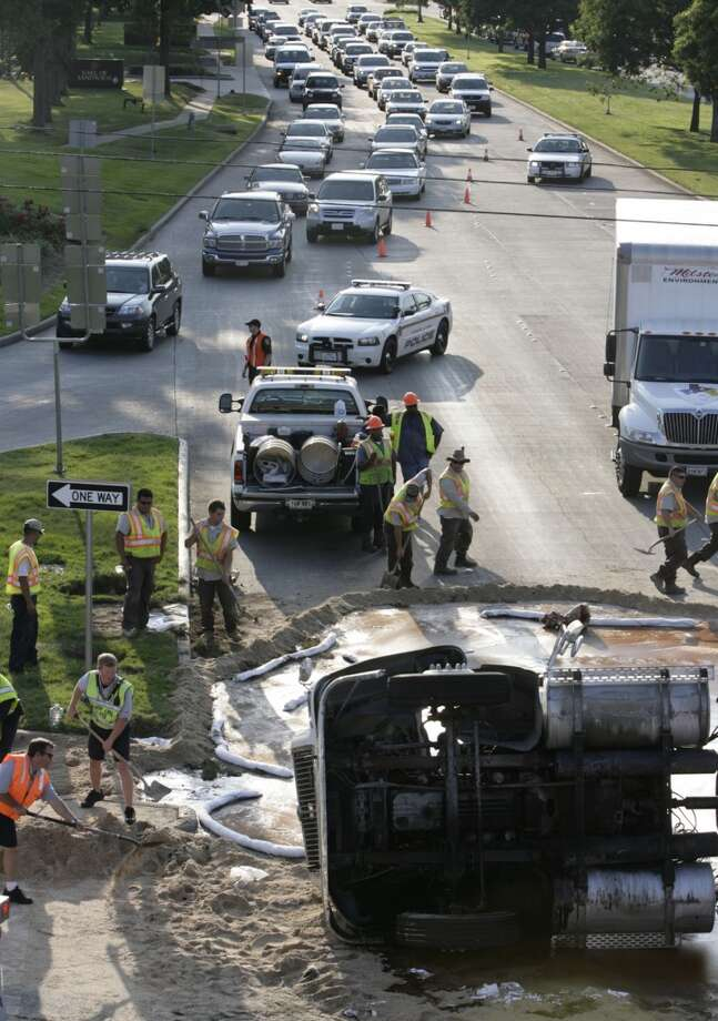 "Crews work on cleaning up 5,000 gallons of molasses spilled from an overturned tanker truck on the intersection of Highway 6 and the Southwest Freeway on Thursday, July 17, 2008, in Sugar Land. The truck was northbound on Highway 6, turning onto the Southwest Freeway feeder road about 4:20 p.m. when the driver ""took too wide of a turn and flipped over,"" said city of Sugar Land spokeswoman Pat Pollicoff. Traffic was diverted from the intersection due to the spill, which is expected to be cleared about 10 p.m. The driver of the truck, Joe Albert Loya, 26, was taken to Sugar Land Methodist Hospital with minor head injuries, Pollicoff said. Molasses is a thick syrup by-product from the processing of the sugarcane or sugar beet into sugar. The spilled molasses was originally slated to be integrated into cattle food. ( Julio Cortez / Chronicle ) Photo: Julio Cortez, Houston Chronicle"