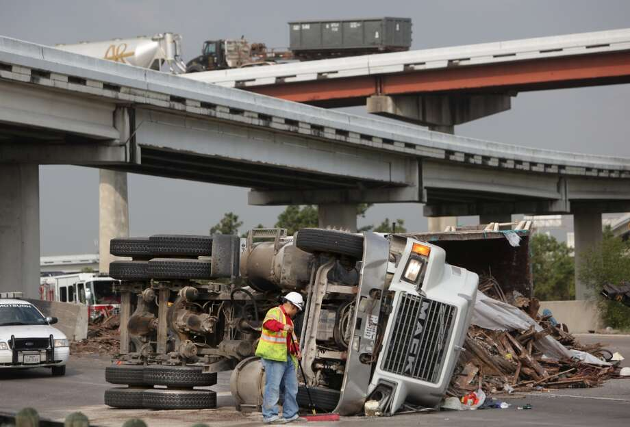 HPD Police and clean up crew responds to an overturned 18 wheeler dumptruck with a lost load of sand, wood,  scrap metal blocks ramp to 610 eastbound is closed along 1-45 at the 610 south loop on Monday, May 21, 2012, in Houston.  ( Mayra Beltran / Houston Chronicle ) Photo: Mayra Beltran, Houston Chronicle