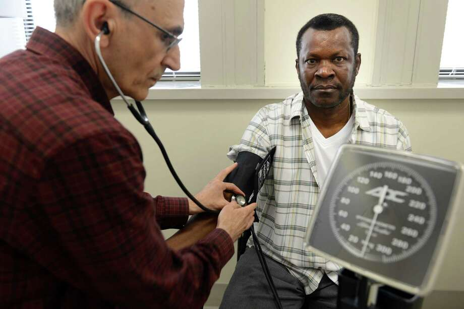 Volunteer nurse Ralph Behlok takes Kenneth Harvey's blood pressure during a visit to the Americares Free Clinic in Bridgeport, Conn., Tuesday, April 29, 2014. Boehringer Ingelheim recently donated free medicine to the clinic for uninsured patients. Photo: Autumn Driscoll / Connecticut Post