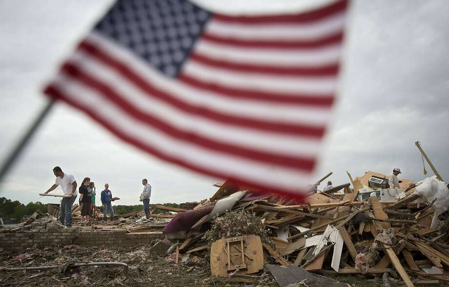 Workers clear debris at Darwin Henry's house in Mayflower, Ark. Henry was grateful that his wife, who died last year, didn't have to witness the destruction. Two days of tornadoes in the South killed 35. Photo: Carlo Allegri, Reuters