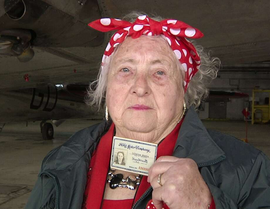 Loraine Osborne, a former Rosie the Riveter, holds up her old Ford Motor Co. identification card. Photo: Mike Householder, Associated Press