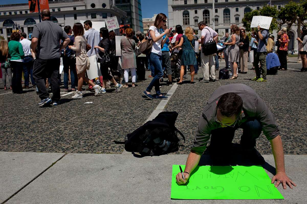 A house share supporter drafts a sign at a rally at the Civic Center Plaza in San Francisco, Calif. on Tuesday, April 29, 2014. Supporters came out to discuss a ballot initiative that would limit short-term rentals in San Francisco.