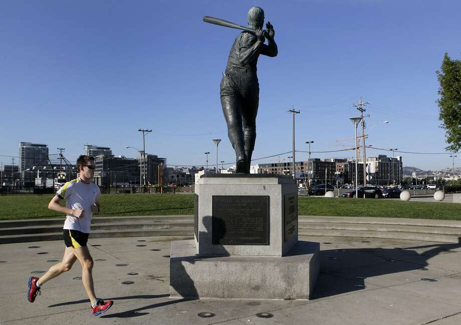 A jogger runs by the The Willie McCovey statue looks over at parking Lot A, across from AT&T Park in San Francisco, Calif. on Tuesday, April 29, 2014. Temperatures will reach well into the 80's in the city today. Photo: Paul Chinn, The Chronicle
