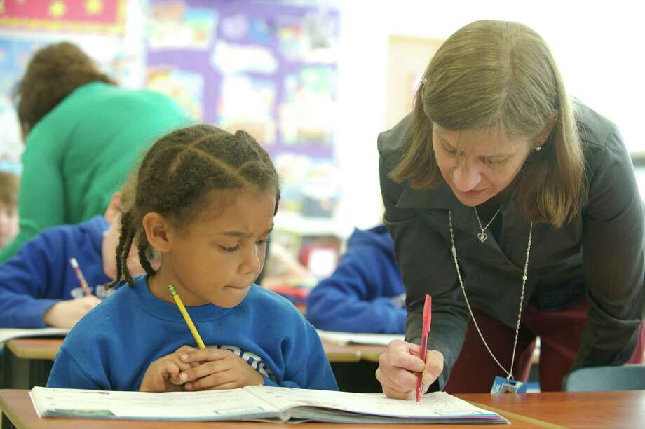 Classroom Assistant Kathy Reisert, helps second grader Lauryn Robinson with her cursive handwriting during class at Saint Gregory the Great School in Danbury, Conn, on Thursday, April 24, 2014. Photo: H John Voorhees III / The News-Times Freelance