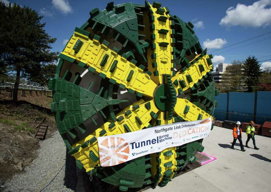 """People walk past the cutter face during the dedication of Sound Transit's tunnel boring machine named """"Brenda."""" The machine is one of two that will dig 3.6 miles of new light rail  tunnels under Seattle from Northgate to the University of Washington  station. The machine was already successfully used to dig the line from downtown Seattle to the future Capitol Hill light rail station. The Northgate station is not planned to open until 2021. Photographed on Monday, April 28, 2014. Photo: JOSHUA TRUJILLO, SEATTLEPI.COM / SEATTLEPI.COM"""