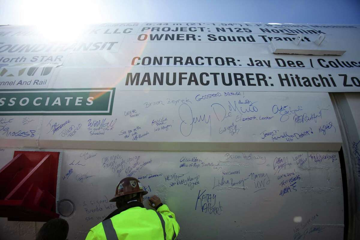 Workers add messages and their signatures during the dedication of Sound Transit's tunnel boring machine named