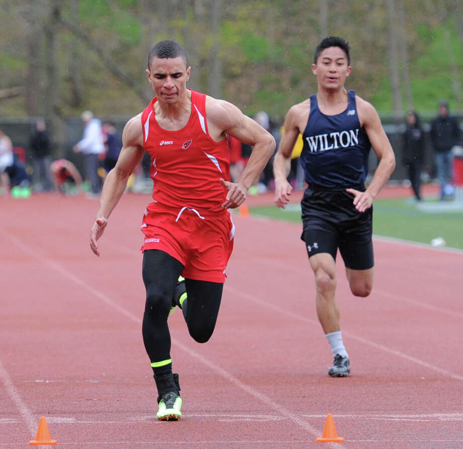 At left, Austin Longi of Greenwich High takes first place in the 100 meter dash beating out Wilton's Marco Agudo, right, during the high school track meet at Greenwich High School, Tuesday, April 29, 2014. Photo: Bob Luckey / Greenwich Time