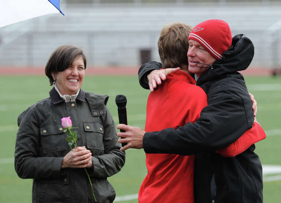 Greenwich High School senior runner Mark Jarombek, center, gets a hug from his coach, Tom Aberle, right, as Jarombek's mother, Liza Jarombek, left, looks on as seniors were honored before the start of the high school track meet at Greenwich High School, Tuesday, April 29, 2014. Photo: Bob Luckey / Greenwich Time