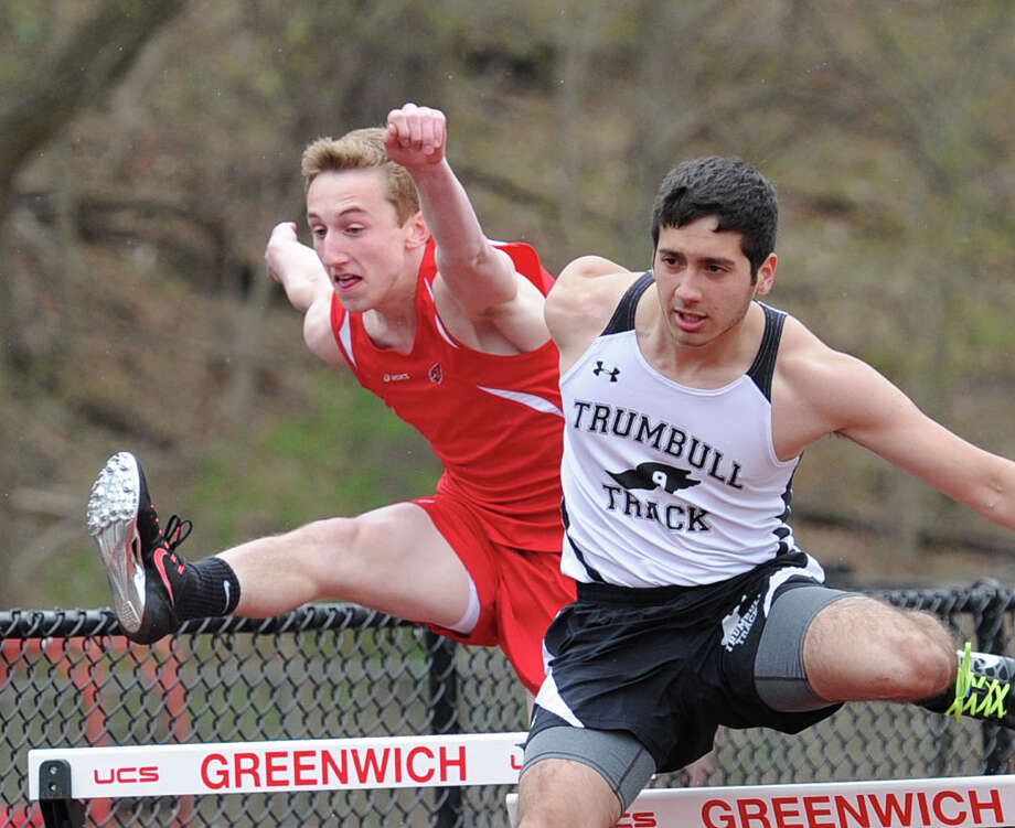 At left, Ian Fulton of Greenwich goes up against Trumbull's Andres Gomez in the 100 meter high hurdles during the high school track meet at Greenwich High School, Tuesday, April 29, 2014. Photo: Bob Luckey / Greenwich Time