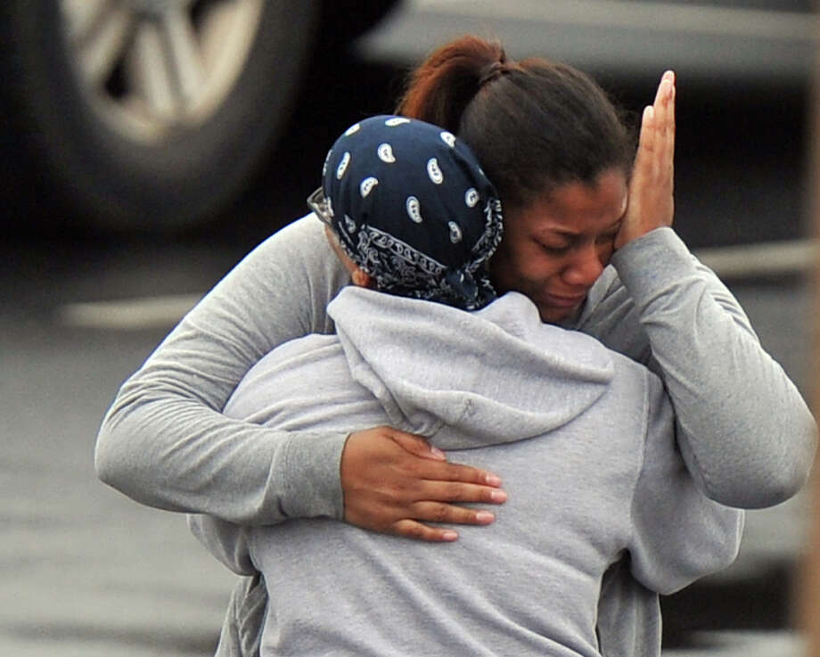 """FedEx employees are reunited with family members Tuesday after a shooting at a package sorting facility in Kennesaw, Ga., where an employee with a shotgun and draped with ammunition """"like Rambo"""" wounded six people and killed himself. Photo: Brant Sanderlin, MBI / Atlanta Journal-Constitution"""