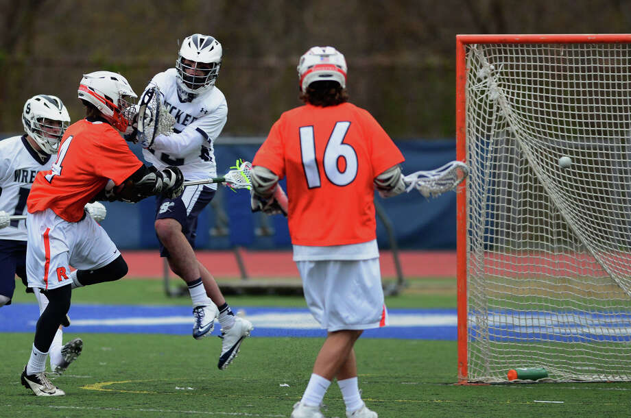 Ridgefield's Matthew Philbin, left, gets the ball past Staples goalie Cole Gendels to score, during boys lacrosse action in Westport, Conn. on Tuesday April 29, 2014. Photo: Christian Abraham / Connecticut Post