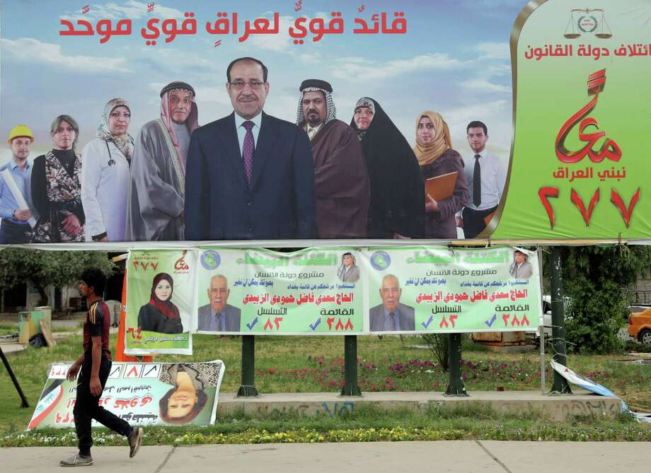 A campaign poster of Iraqi Prime Minister Nouri al-Maliki oversees passers-by in Baghdad, Iraq. Al-Maliki will likely to rely on a narrow sectarian Shiite base as he seeks a third term Wednesday. Photo: Khalid Mohammed, STF / AP