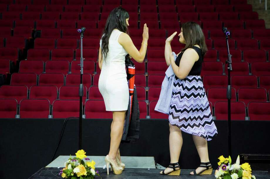 Yes Prep Southeast High School's students Florencia Rangel, left, 18, high fives her classmate Ana Reyna, right, 18, after announcing the colleges they are going this coming school year during the Yes Prep Signing Day, Tuesday, April 29, 2014, at the Toyota Center in Houston. Rangel has been admitted to Texas Tech and Reyna will be going to the University of Houston Clear Lake. Photo: Marie D. De Jesus, Houston Chronicle / © 2014 Houston Chronicle