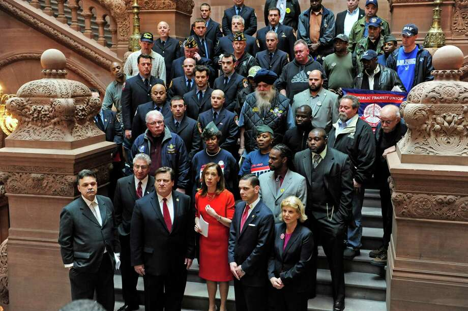 Assembly members front row from left to right: Felix Ortiz, James Tedisco, Edward Hennessey, Amy Paulin, Angelo Santabarbara and Shelley Mayer, with members of veterans' groups and unions behind them take part in a press conference held on the Million Dollar Staircase at the Capitol on Tuesday, April 29, 2014, in Albany, N.Y.  The press even was held by legislators, union members and veterans to express their support for the Military Buyback Bill.  The bill would amend the New York State Retirement and Social Security Law to allow all public sector workers who were honorably discharged from the military to purchase up to three years of credit towards their pension.   (Paul Buckowski / Times Union) Photo: Paul Buckowski / 00026674A