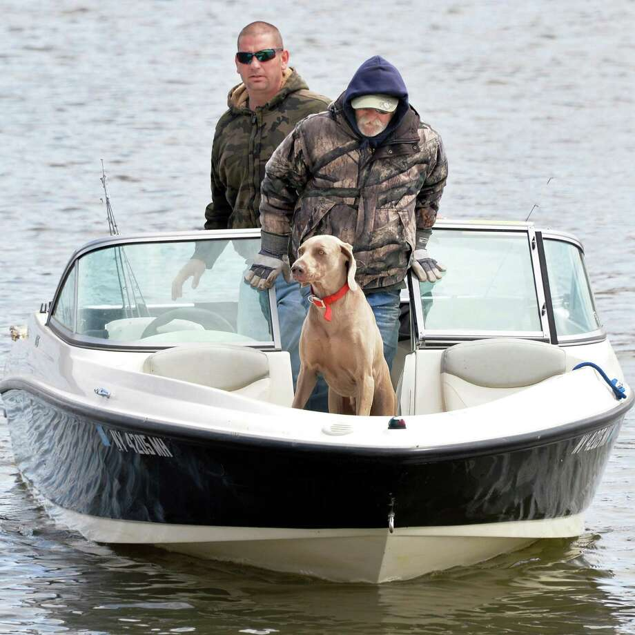Daniel Brown, left, his Uncle Gerald Brown and Bentley head back to the boat launch after a morning of fishing for stripers on the Hudson River Tuesday April 29, 2014, in Albany, N.Y.  (John Carl D'Annibale / Times Union) Photo: John Carl D'Annibale / 00026659A