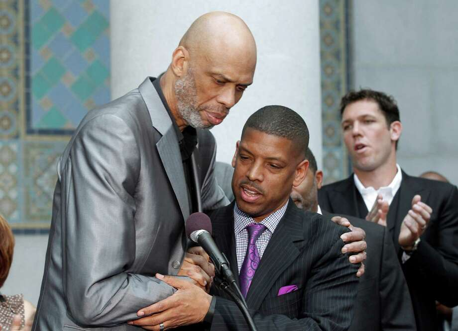 Sacramento, Calif., Mayor Kevin Johnson, center, and Hall of Famer Kareem Abdul-Jabbar embrace during a news conference outside City Hall in Los Angeles Tuesday, April 29, 2014, after Johnson's comments on the decision by NBA commissioner Adam Silver to ban Los Angeles Clippers owner Donald Sterling from basketball for life in response to racist comments the league says Sterling made in a recorded conversation. Former NBA player Luke Walton applauds at rear right rear. (AP Photo) ORG XMIT: LA106 / AP