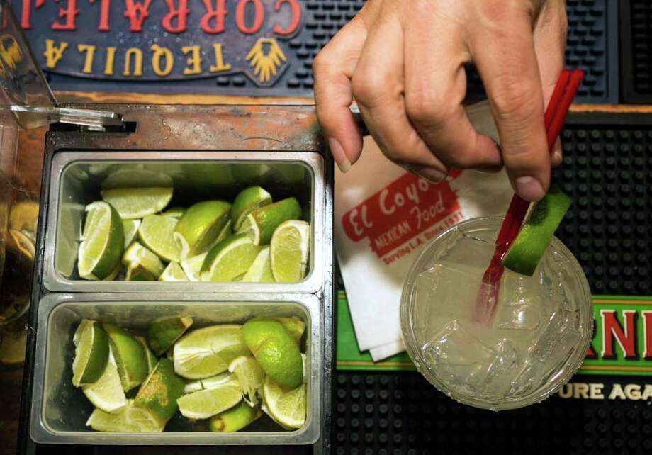 As the industry waits for the summer crop to lower prices, some bars are cutting happy hour lime drinks. Photo: STF / AP