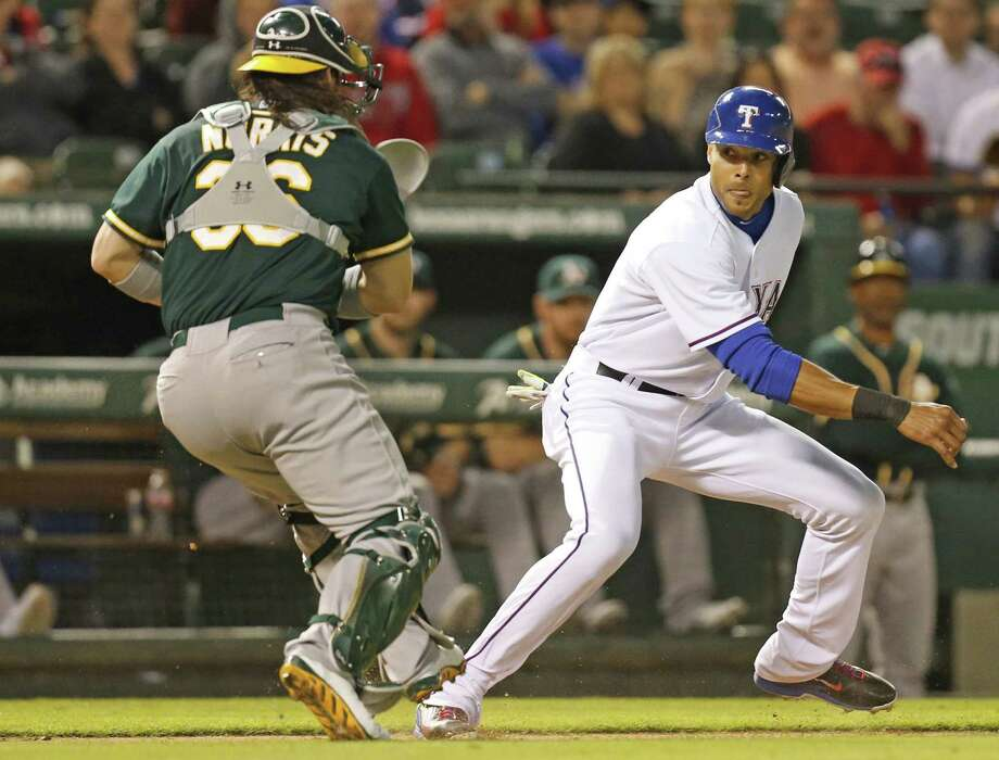 The Texas Rangers' Alex Rios, right, gets caught in a rundown between third and home as Oakland Athletics catcher Derek Norris pursues in the fourth inning at Globe Life Park in Arlington, Texas, on Tuesday, April 29, 2014. (Louis DeLuca/Dallas Morning News/MCT) Photo: Louis DeLuca, McClatchy-Tribune News Service / Dallas Morning News