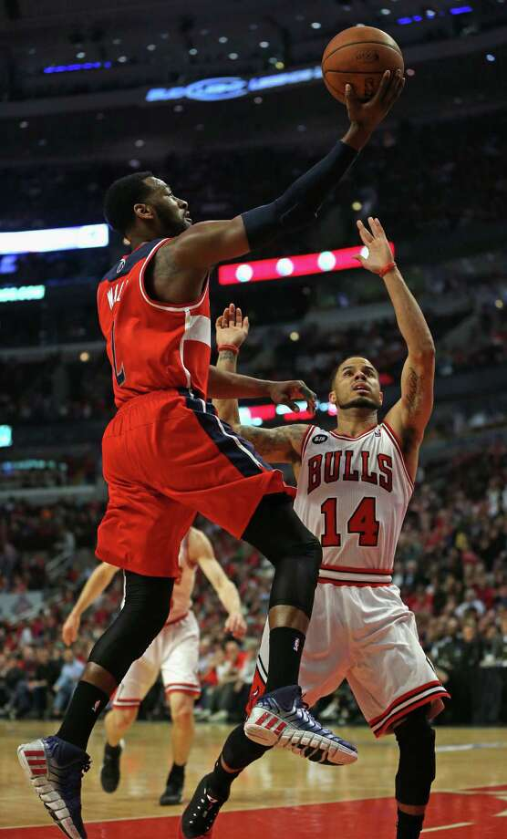 CHICAGO, IL - APRIL 29: John Wall #2 of the Washington Wizards drives past D.J. Augustin #14 of the Chicago Bulls in Game Five of the Eastern Conference Quarterfinals during the 2014 NBA Playoffs at the United Center on April 29, 2014 in Chicago, Illinois. NOTE TO USER: User expressly acknowledges and agrees that, by downloading and or using this photograph, User is consenting to the terms and conditions of the Getty Images License Agreement. (Photo by Jonathan Daniel/Getty Images) ORG XMIT: 485876411 Photo: Jonathan Daniel / 2014 Getty Images
