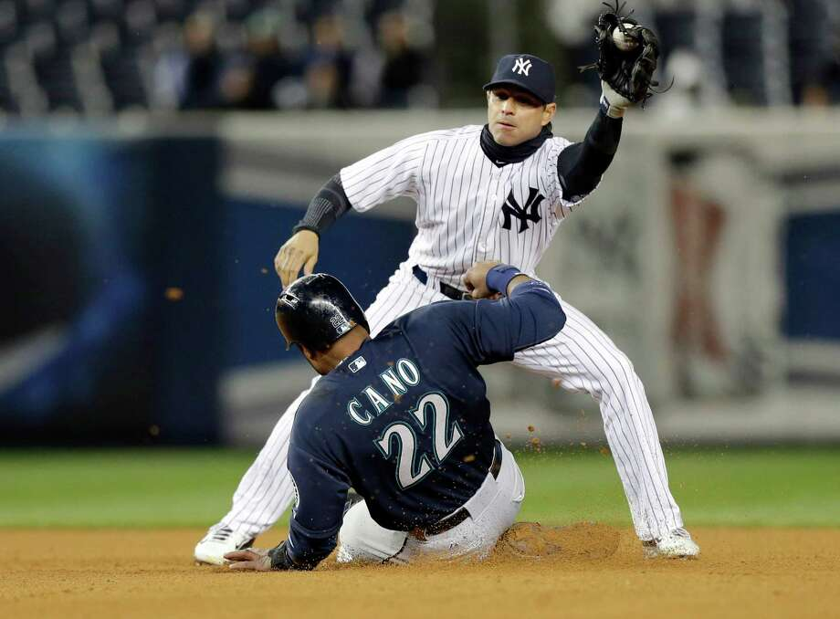 Seattle Mariners second baseman Robinson Cano (22) steals second base as New York Yankees second baseman Brian Roberts attempts to tag him out during the seventh inning of a baseball game Tuesday, April 29, 2014, in New York. (AP Photo) ORG XMIT: NYY115 Photo: Frank Franklin II / AP