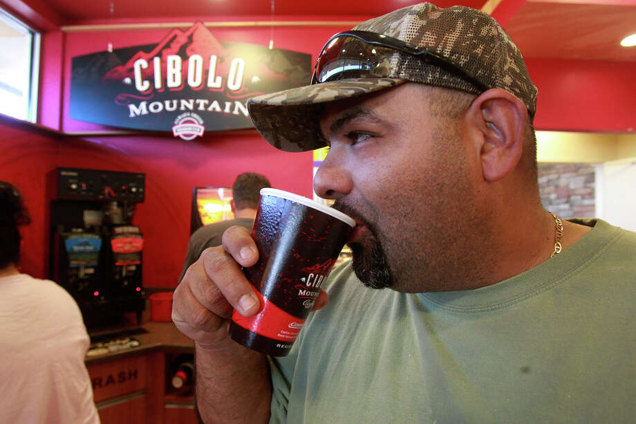Julio Trevino enjoys a free cup of java Tuesday April 29, 2014 at the Valero at UTSA Blvd. and IH-10. Valero offer free coffee when the Spurs win playoff games and during the NBA Finals. Photo: San Antonio Express-News / ©San Antonio Express-News/John Davenport