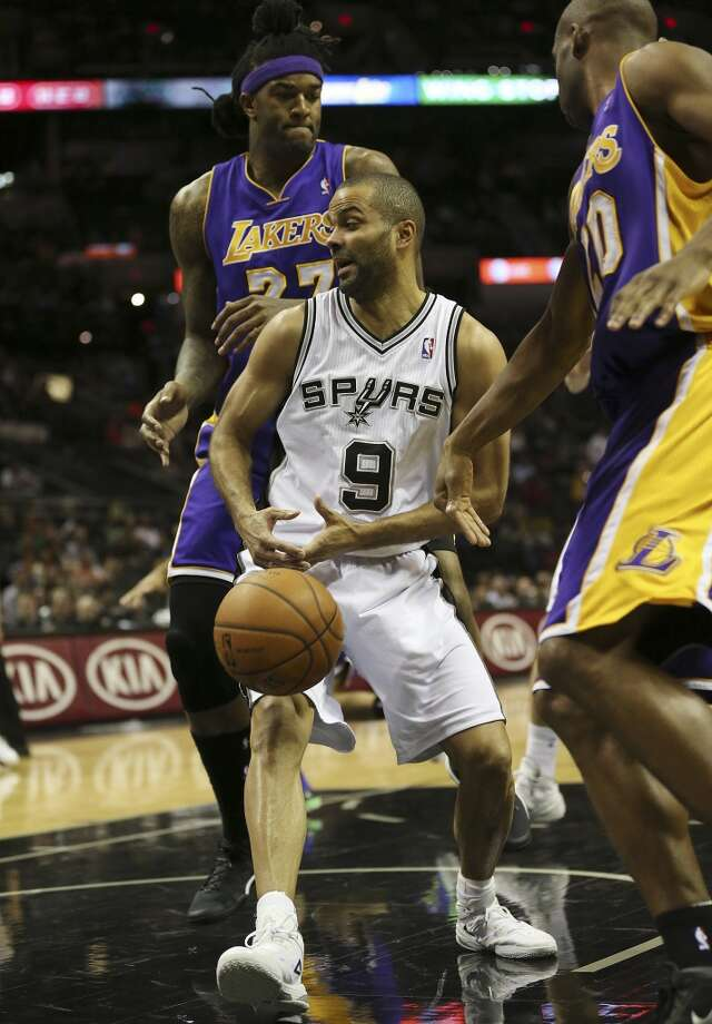 San Antonio Spurs' Tony Parker looses control of the ball under pressure from Los Angeles Lakers' Jordan Hill, left, and Jodie Meeks during the first half at the AT&T Center, Wednesday, April 16, 2014. Photo: Jerry Lara, San Antonio Express-News