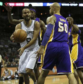 San Antonio Spurs' Tony Parker passes around Los Angeles Lakers' Robert Sacre during the first half at the AT&T Center, Wednesday, April 16, 2014. Photo: Jerry Lara, San Antonio Express-News