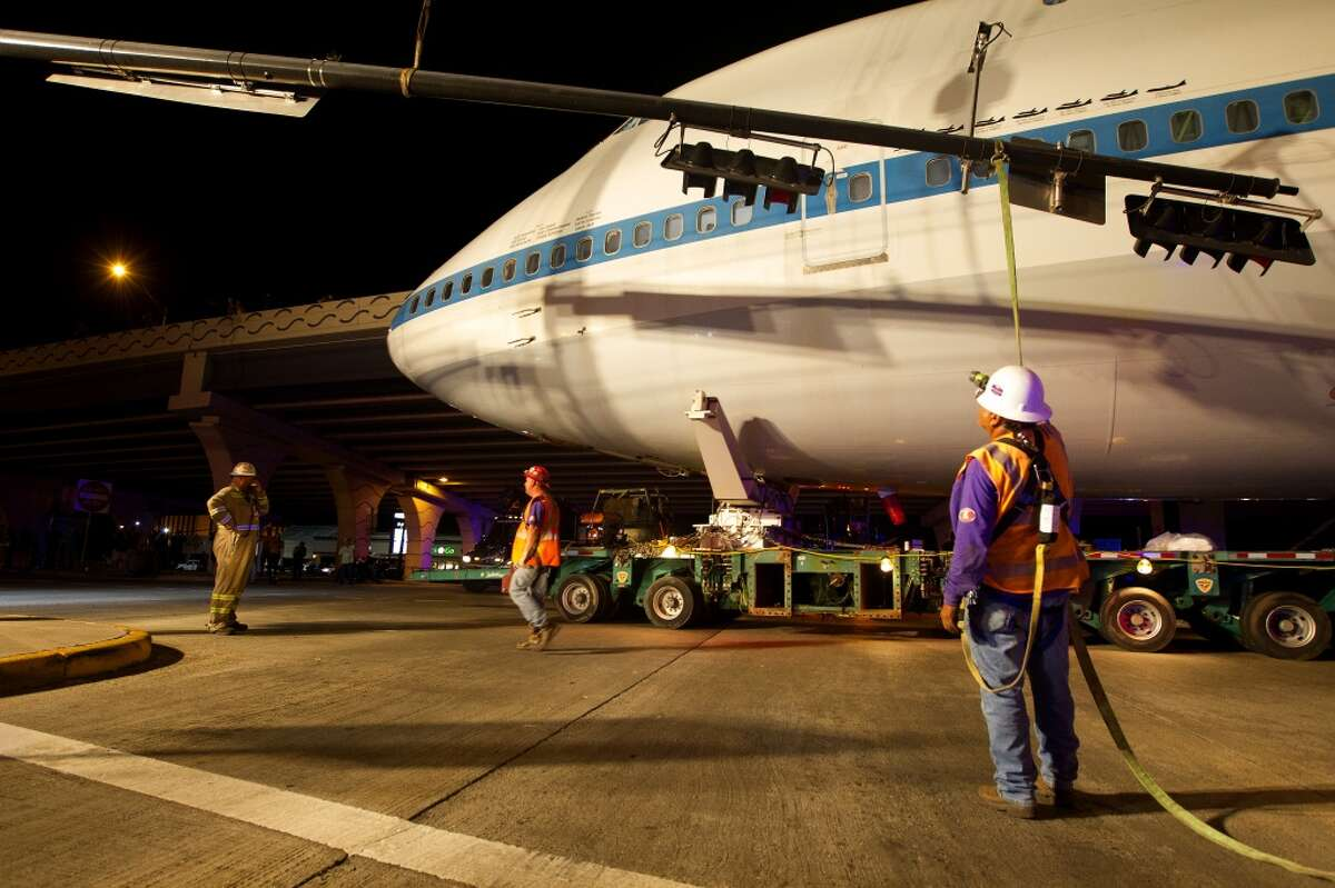 Crews move traffic lights to permit the plane to pass along East NASA Parkway on April 29.